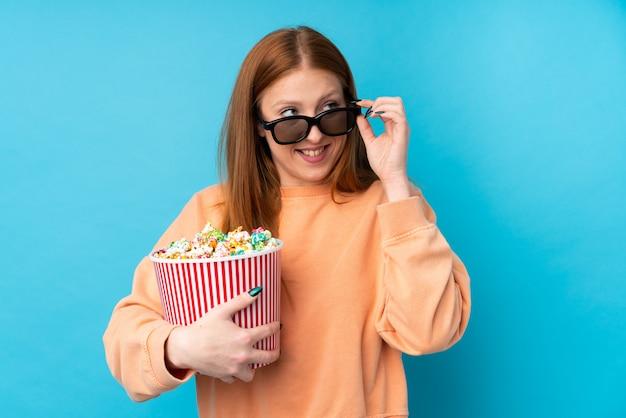 Junge rothaarige frau über isolierter wand mit 3d-brille und hält einen großen eimer popcorn