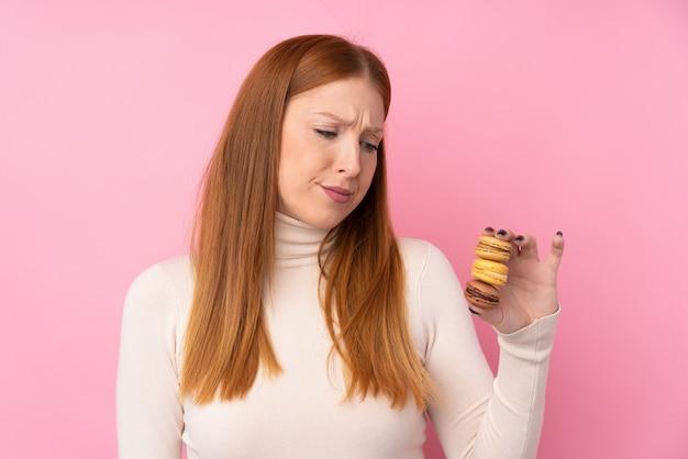 Junge rothaarige frau über rosa, die bunte französische macarons mit traurigem ausdruck hält