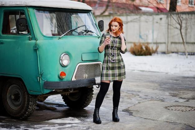Junge rothaarige frauendame mit dem handy und kopfhörern, tragend auf überprüftem kleid im alten weinleseminivanbus.