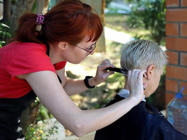 Junge rothaarige friseurin macht der frau im freien einen kurzen haarschnitt mit einer schere