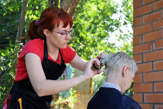 Junge rothaarige friseurin macht der frau im freien einen kurzen haarschnitt