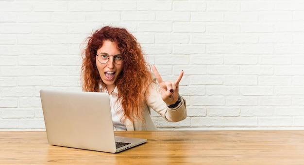 Junge rothaarige lockige frau, die mit ihrem laptop arbeitet, der eine hörnergeste als ein revolutionskonzept zeigt.