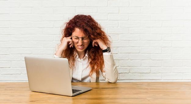 Junge rothaarige lockige frau, die mit ihrem laptop arbeitet, der ohren mit händen bedeckt.