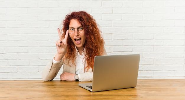 Junge rothaarige lockige frau, die mit ihrem laptop arbeitet, der siegeszeichen zeigt und breit lächelt.