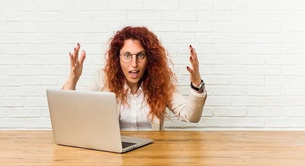Junge rothaarige lockige frau, die mit ihrem laptop arbeitet, empfängt eine angenehme überraschung, aufgeregt und hebt die hände