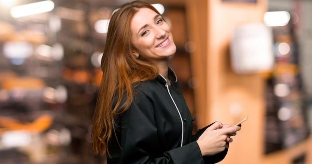 Junge rothaarigecheffrau, die eine mitteilung mit dem mobile in der bäckerei sendet