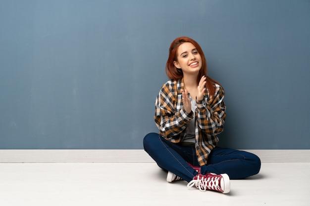 Junge rothaarigefrau, die auf dem boden applaudiert nach darstellung in einer konferenz sitzt