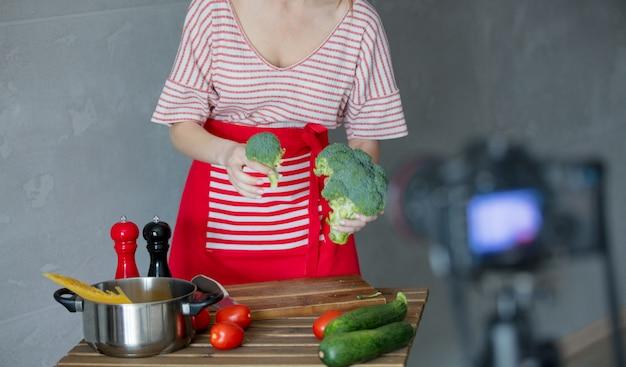 Junge rothaarigefrau, die video kochend macht