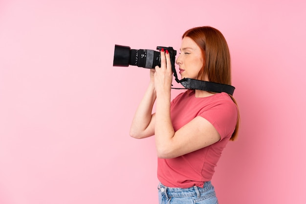 Junge rothaarigefrau mit einer berufskamera