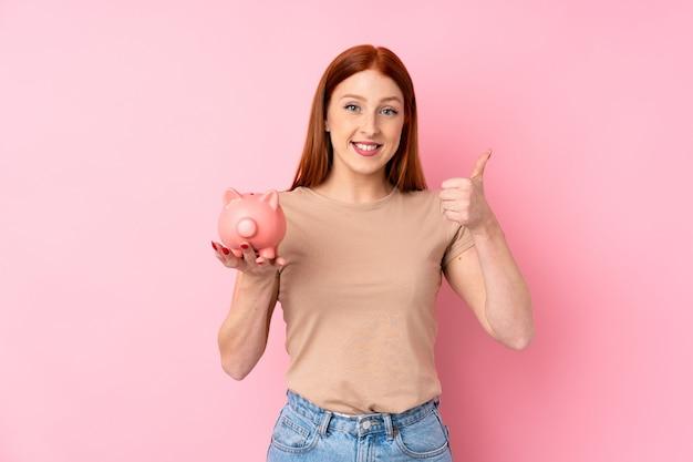 Junge rothaarigefrau über dem lokalisierten rosa hintergrund, der ein großes sparschwein hält