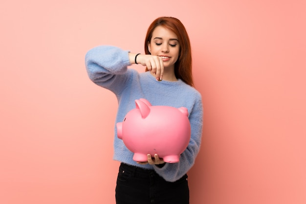 Junge rothaarigefrau über dem rosa, das ein sparschwein nimmt und glücklich, weil es voll ist