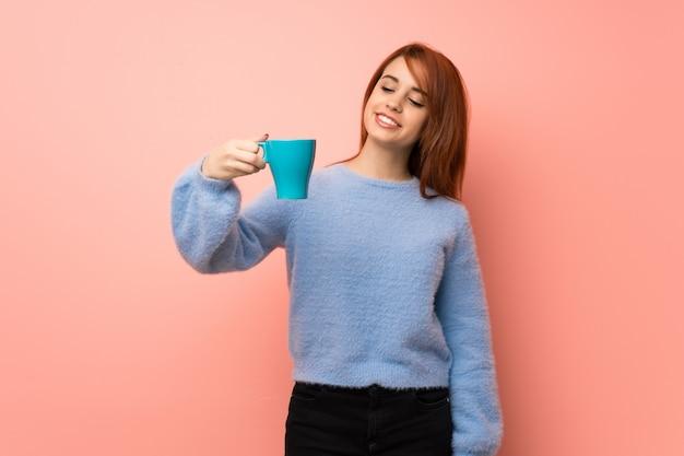 Junge rothaarigefrau über dem rosa, das einen heißen tasse kaffee hält