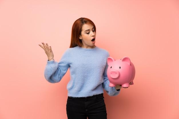 Junge rothaarigefrau über dem rosa überrascht beim halten eines sparschweins
