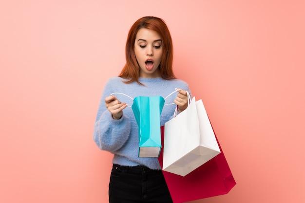 Junge rothaarigefrau über dem rosa überrascht beim halten vieler einkaufstaschen