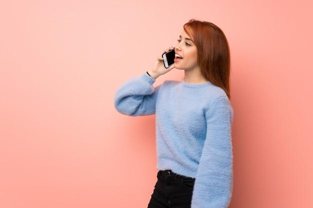 Junge rothaarigefrau über der rosa wand, die ein gespräch mit dem handy hält