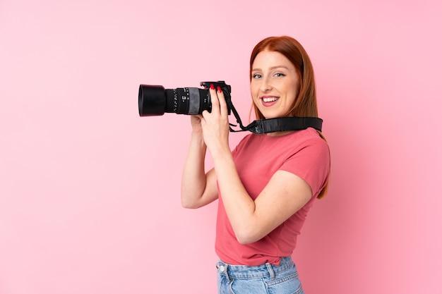 Junge rothaarigefrau über lokalisiertem rosa mit einer berufskamera