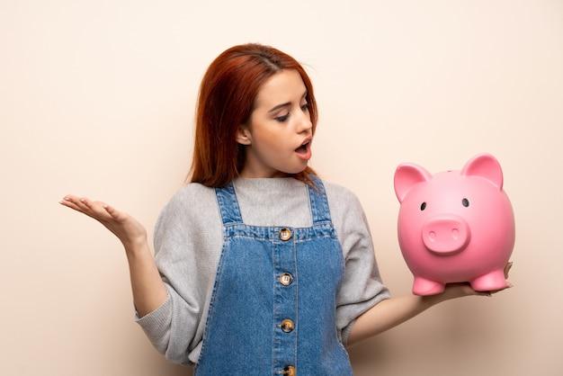 Junge rothaarigefrau über lokalisiertem überrascht beim halten eines sparschweins