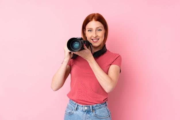 Junge rothaarigefrau über lokalisierter rosa wand mit einer berufskamera