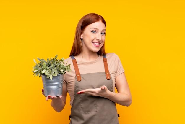 Junge rothaarigegärtnerfrau, die die hände einer betriebsverlängerung zur seite hält, damit die einladung kommt