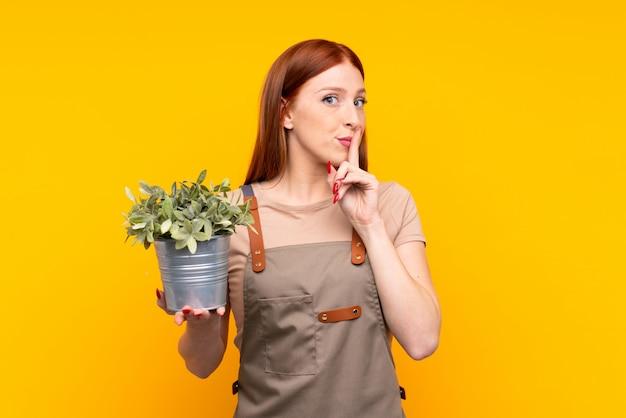 Junge rothaarigegärtnerfrau, die eine anlage über der lokalisierten gelben wand tut ruhegeste hält
