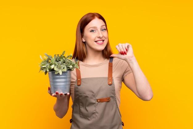 Junge rothaarigegärtnerfrau, die eine anlage über lokalisiertem gelb stolz und selbstzufrieden hält
