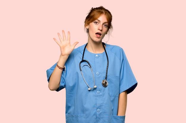 Junge rothaarigekrankenschwester, die fünf mit den fingern über rosa hintergrund zählt