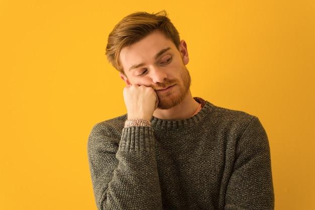 Junge rothaarigemann-gesichtsnahaufnahme, die an etwas, schauend zur seite denkt