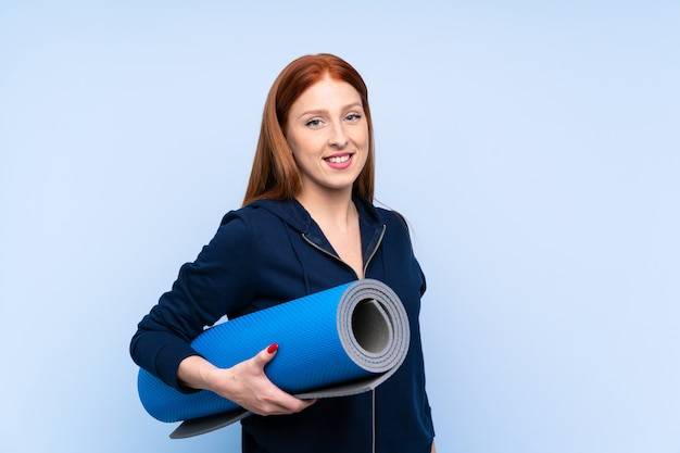 Junge rothaarigesportfrau über lokalisiertem blauem hintergrund mit einer matte und einem lächeln