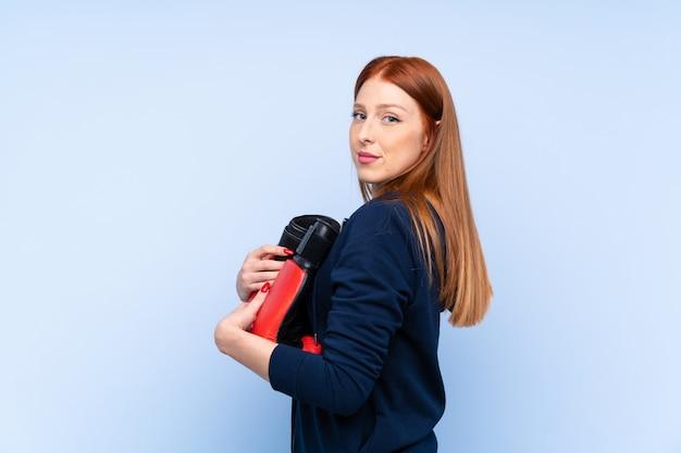 Junge rothaarigesportfrau über lokalisierter blauer wand mit boxhandschuhen
