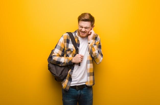 Junge rothaarigestudenten-mannbedeckungsohren mit den händen
