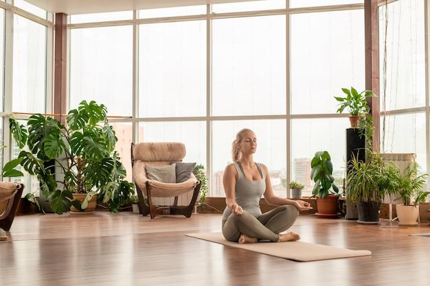 Junge ruhige blonde frau in der sportbekleidung, die beine kreuzt, während auf matte in der pose des lotus sitzend und meditationsübungen zu hause praktiziert
