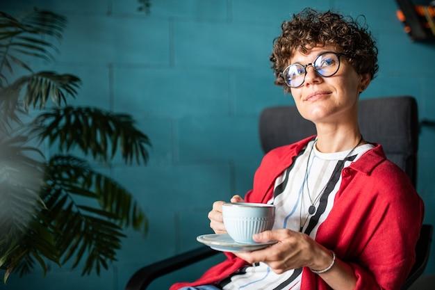 Junge ruhige elegante frau mit tasse tee oder kaffee, die im café in der mittagspause oder nach dem arbeitstag entspannen