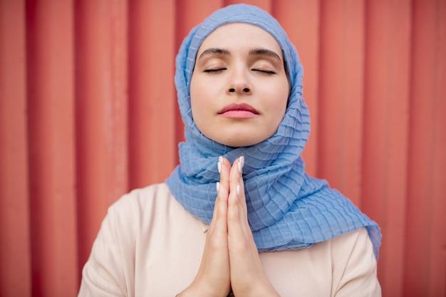 Junge ruhige frau im hijab, die ihre hände unter kinn zusammengesetzt hält, während sie yoga praktiziert