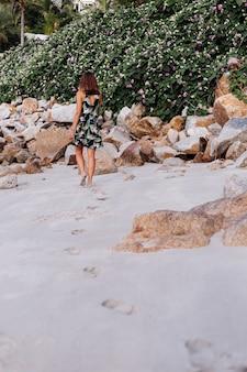 Junge ruhige tätowierte frau im kurzen kleid des tropischen sommerdrucks am felsigen strand mit grünem busch und lila rosa blumen