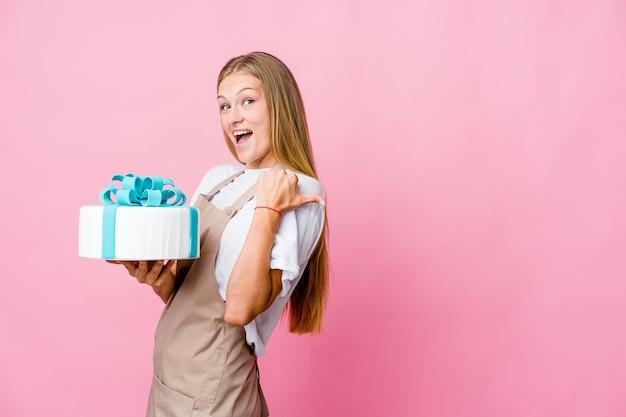 Junge russische bäckerin, die eine köstliche kuchenspitze mit daumenfinger weg hält, lachend und sorglos.