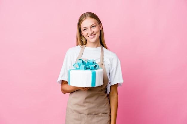 Junge russische bäckerin, die einen köstlichen kuchen glücklich, lächelnd und fröhlich hält.