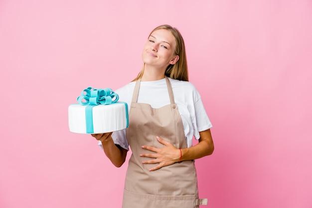 Junge russische bäckerin, die einen köstlichen kuchen hält, berührt bauch, lächelt sanft