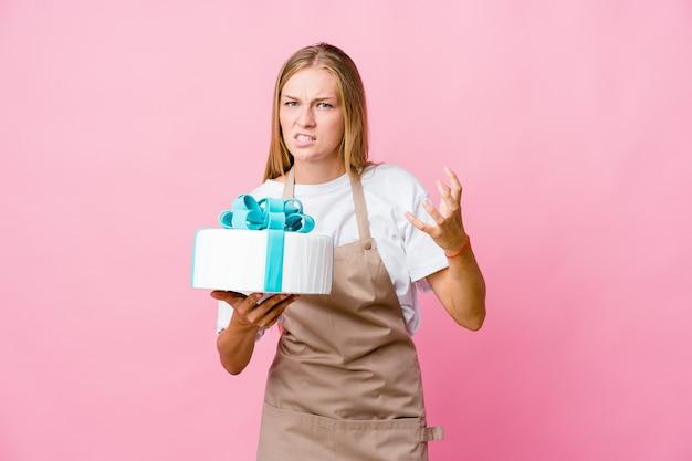 Junge russische bäckerin, die einen köstlichen kuchen verärgert hält, der mit angespannten händen schreit.