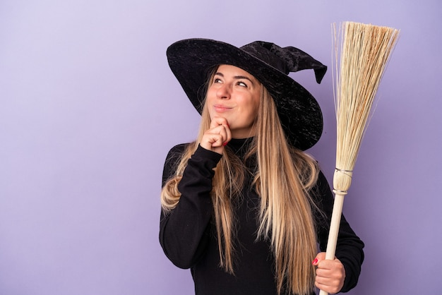 Junge russische frau, die als hexe verkleidet ist und einen besen hält, der auf violettem hintergrund isoliert ist und seitlich mit zweifelhaftem und skeptischem ausdruck schaut.