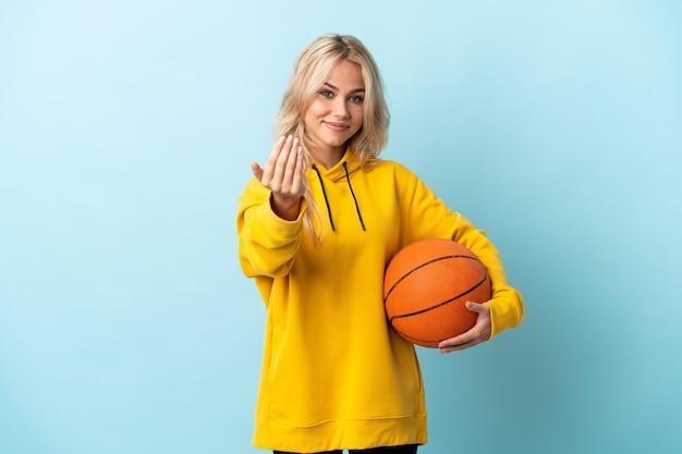 Junge russische frau, die basketball lokalisiert auf blauer wand einlädt, mit hand zu kommen. schön, dass du gekommen bist