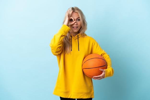Junge russische frau, die basketball lokalisiert auf blauer wand spielt, die ok zeichen mit fingern zeigt