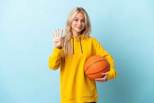 Junge russische frau, die basketball spielt, isoliert auf blau glücklich und zählt vier mit den fingern