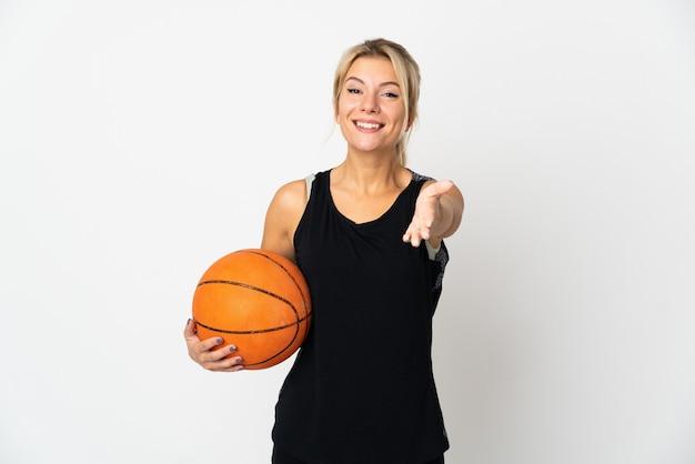 Junge russische frau, die basketball spielt, isoliert auf weißem hintergrund, händeschütteln, um ein gutes geschäft abzuschließen?