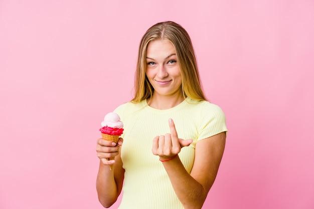 Junge russische frau, die ein eis isst, das isoliert mit dem finger auf sie zeigt, als ob die einladung näher kommt.