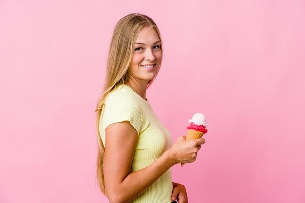 Junge russische frau, die ein eis isst, sieht beiseite lächelnd, fröhlich und angenehm aus.