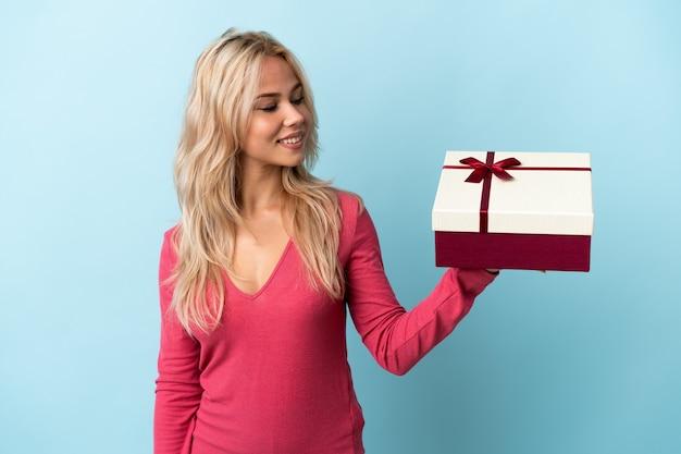 Junge russische frau, die ein geschenk lokalisiert auf blau mit glücklichem ausdruck hält