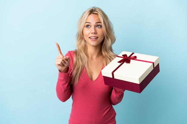 Junge russische frau, die ein geschenk lokalisiert auf blauer wand hält, das beabsichtigt, die lösung zu realisieren, während ein finger anhebt