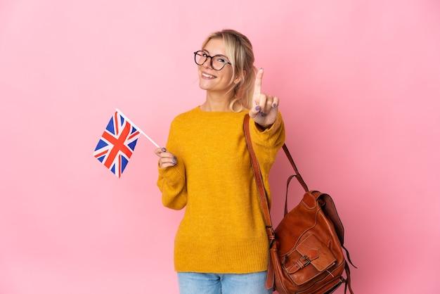 Junge russische frau, die eine britische flagge lokalisiert auf rosa hintergrund zeigt und einen finger hebt