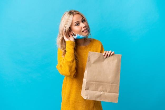 Junge russische frau, die eine einkaufstasche des lebensmittels lokalisiert auf der blauen wand hält, die etwas hört, indem man hand auf das ohr legt