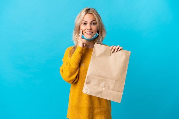 Junge russische frau, die eine einkaufstasche des lebensmittels lokalisiert auf der blauen wand hält, die mit einem glücklichen und angenehmen ausdruck lächelt
